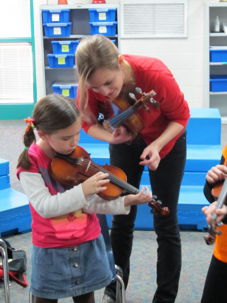 A HHSOM student teaches a young string player